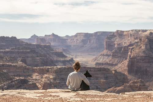 nature person with dog sitting on Grand Canyon cliff canyon