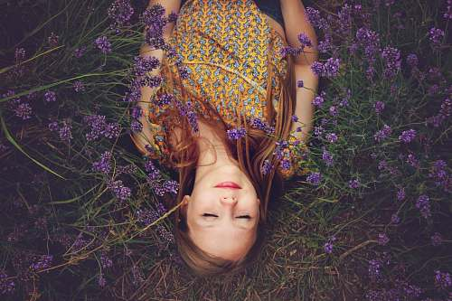 woman woman in yellow and teal top sleeping beside lavenders girl