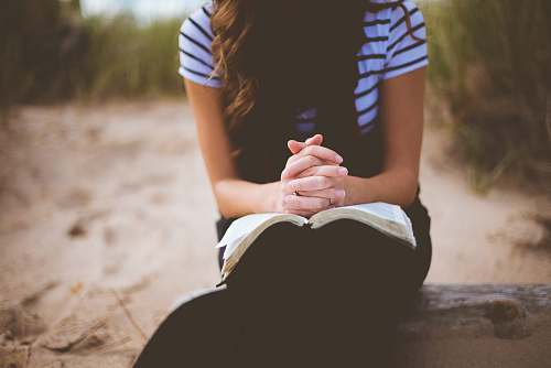 person woman sitting on brown bench while reading book prayer