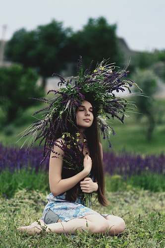 woman woman wearing lavender headdress sitting on grass girl