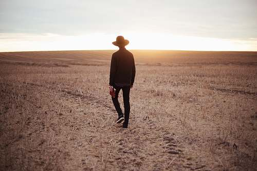 people man walking on dried plain while looking towards the sun on horizon human
