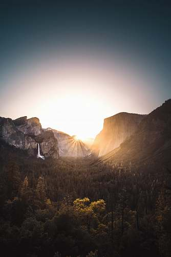 nature gray mountain surrounded with trees during sunrise sunset