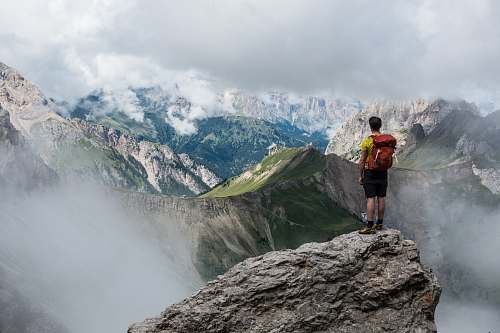 nature man with red backpack standing on cliff facing mountains under white sky during daytime hiking