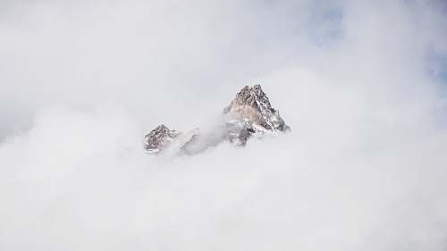 grey snow mountain covered with clouds peak