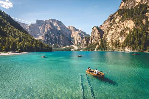 photo landscape three brown wooden boat on blue lake water taken at daytime italy free for commercial use images