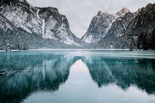 nature body of water and snow-covered mountains during daytime snow