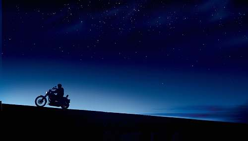 motorcycle person riding motorcycle under blue and black skies during night time vehicle
