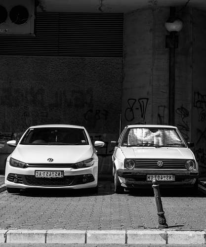 car grayscale photo of two Volkswagen cars parked on sidewalk automobile