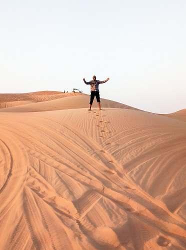 outdoors man standing on brown desert during daytime soil