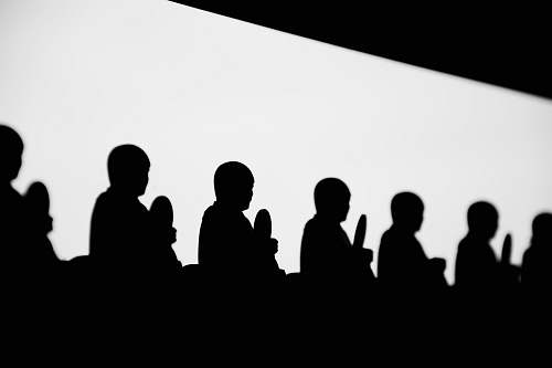 black-and-white silhouette of praying people audience
