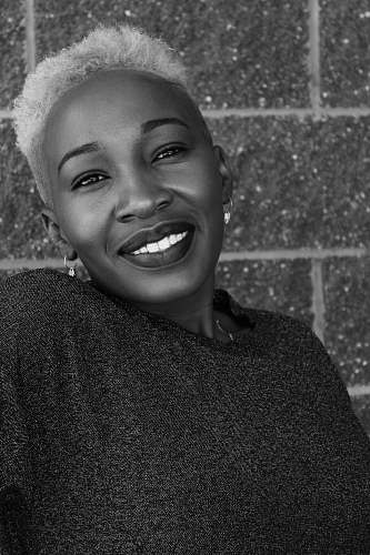 clothing smiling woman by wall black-and-white