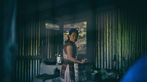 human woman in apron standing near cooking pots person