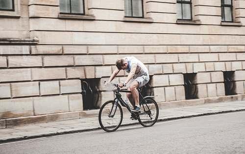 bicycle man wearing gray t-shirt and gray shorts cycling bike