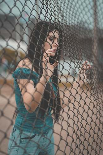 person photography of woman touching gray metal fence people