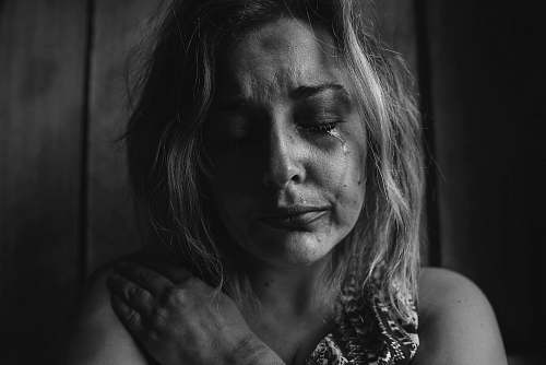 human grayscale photo of woman crying holding her right chest black-and-white