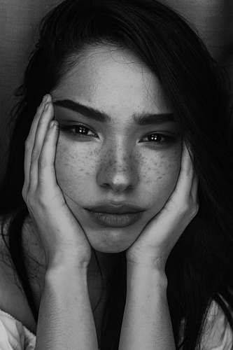 black-and-white grayscale photography of woman with two hands on her face portrait