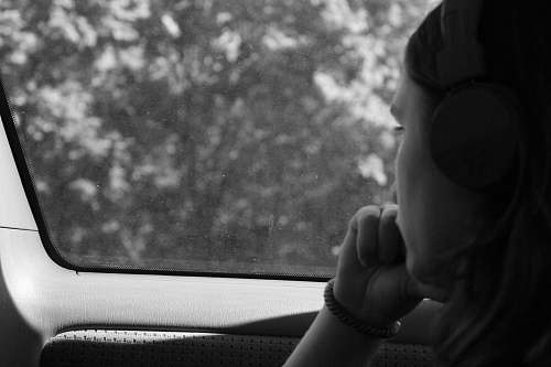 people grayscale photo of woman inside car black-and-white
