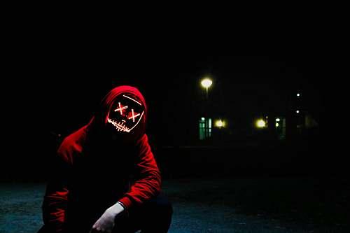 human man squatting during nighttime people