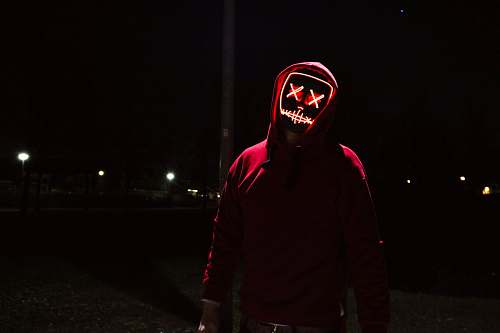 human person wearing black mask standing near post people
