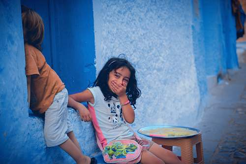 human two children leaning on blue wall people