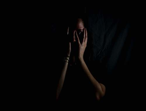human woman holding her face in dark room woman