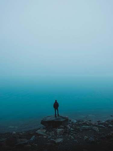 blue man standing on rock near body of water standing