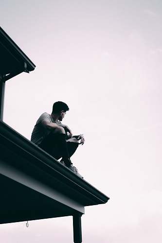 person grayscale photography of man sitting on dock banister