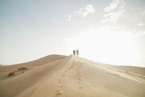 nature person walking on desert during daytime outdoors