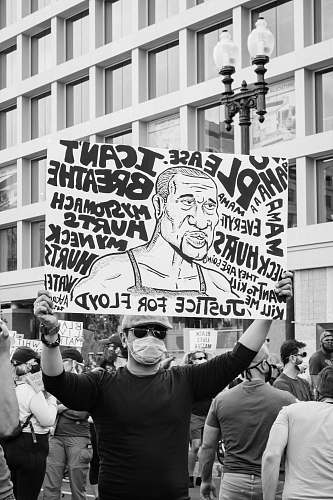 protest grayscale photo of man holding happy birthday signage parade