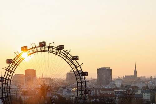 austria ferris wheel near city buildings during sunset amusement park