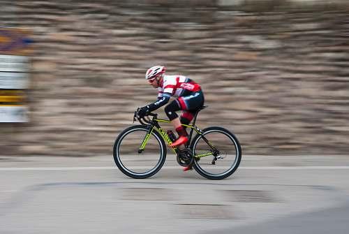 bicycle man riding green and black road bike during daytime sport