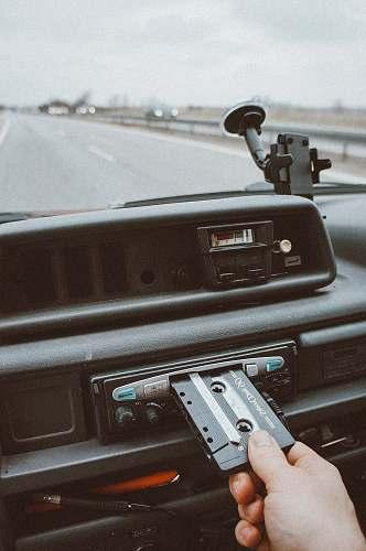 roadtrip person inserting cassette tape on cassette player tape