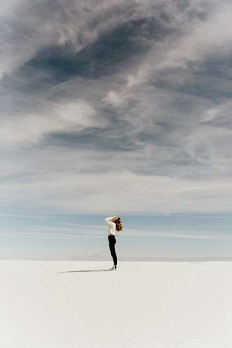 woman woman looking up to the sky while standing on white sand minimal