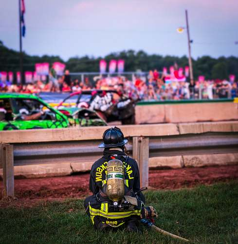 human firefighter sitting on grass near stock cars on road fireman