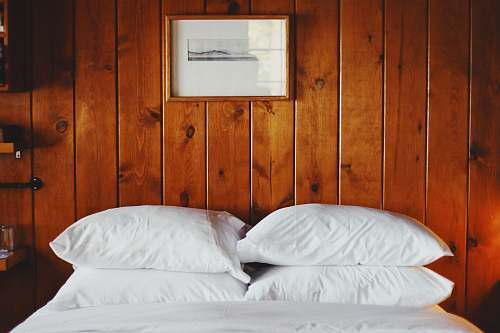 pillow four white pillows in front of brown wooden wall wood