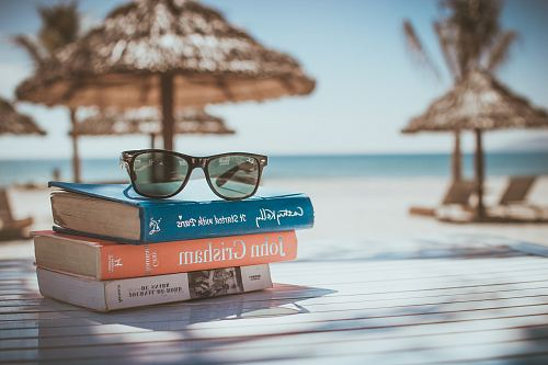 photo black framed Ray-Ban Wayfarer sunglasses on top of book free for commercial use images