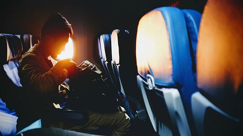 photo man looking on his sitting on plane seat free for commercial use images