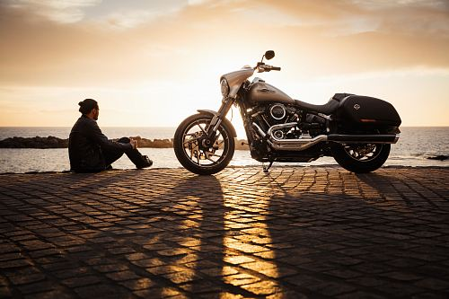 photo man sitting on ground beside parked silver cruiser motorcycle free for commercial use images