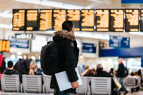 photo man standing inside airport looking at LED flight schedule bulletin board free for commercial use images