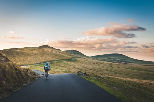 photo person cycling on road distance with mountain during daytime free for commercial use images