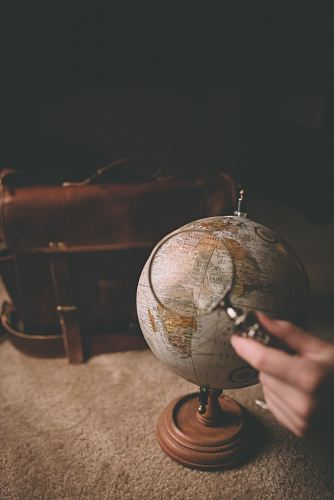 photo person holding magnifying glass near desk globe free for commercial use images