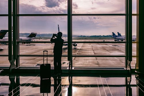 photo silhouette of person standing in front of glass while taking photo of plane free for commercial use images
