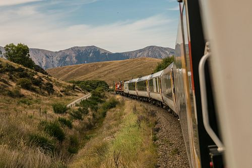white train with the distance of mountain during daytime