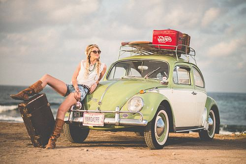 photo woman leaning on green and white Volkswagen Beetle near sea under white sky during daytime free for commercial use images