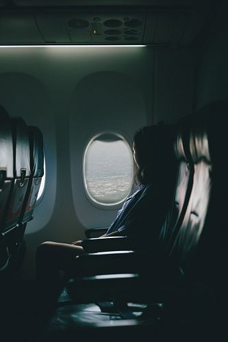 photo woman sits on seat near window inside plane free for commercial use images