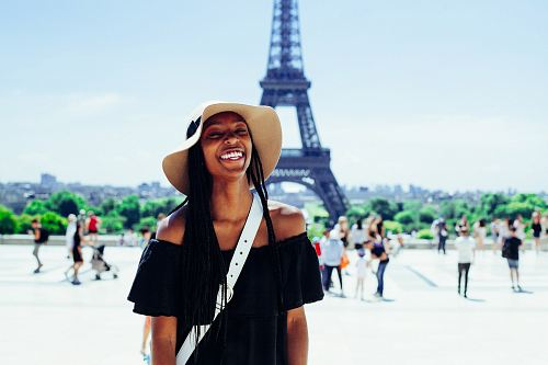 woman standing behind Eiffel Tower during daytime