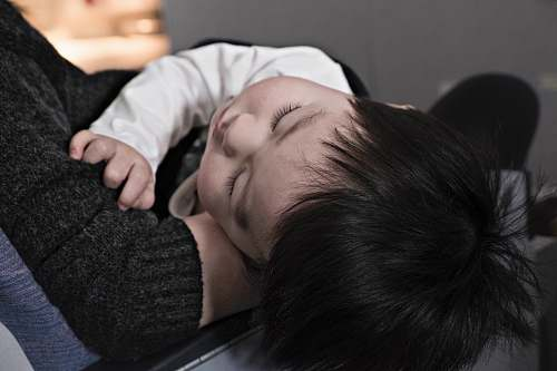 asian toddler sleeping on parent family