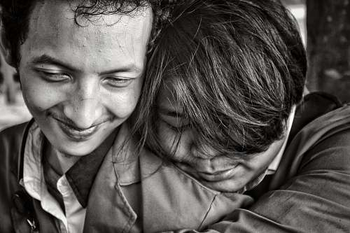 people greyscale photo of two people close to each other human