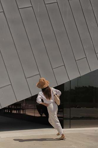 apparel woman standing outside building hat