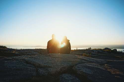 sunset silhouette of two person during sunrise sunlight